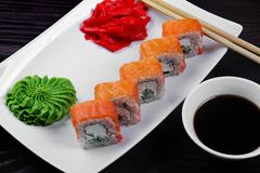 Philadelphia sushi rolls on a white square plate with wasabi, soy sauce and ginger. Dark wooden background.  stock image