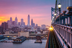 Philadelphia under a hazy purple sunset. An incoming train crosses Ben Franklin Bridge Stock Photography