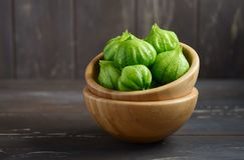 Philadelphica vert organique frais de Physalis de tomatillos avec une cosse sur la table en bois rustique Photo stock