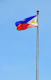 The Philippine Flag. The flag of the Republic of the Philippines waving on a flagpole against a still blue sky Stock Photo