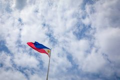 Philippine flag against blue sky. Philippine flag on a pole against blue sky royalty free stock image