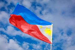 Philippines flag waving in the sky. Philippine flag on a pole against blue sky stock photo