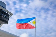 Philippines flag waving in the sky. Philippine flag on a pole against blue sky royalty free stock images
