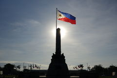 Philippine Flag Rizal Monument. Philippine flag and Jose Rizal monument with sun rays as backdrop that lights up the waving Philippine flag royalty free stock photography