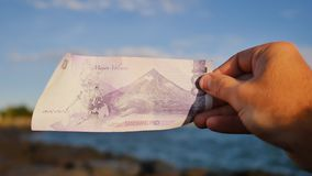 Philippine money. A Filipino monetary note in one hundred pesos is dedicated to the Mayon volcano. Philippine money. A Filipino monetary note in one hundred stock video footage