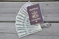 Philippine passport over US dollars. In a wooden background