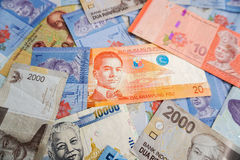 Philippine peso among different asian currencies. Philippine peso in pile of different asian currency banknotes Royalty Free Stock Photos
