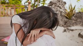 An philippine schoolgirl girl with a backpack is sitting and crying near the tropical coast. Sad mood. An philippine schoolgirl girl with a backpack is sitting stock video