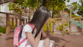 An philippine schoolgirl girl with a backpack is sitting and crying near the tropical coast. Sad mood. An philippine schoolgirl girl with a backpack is sitting stock footage