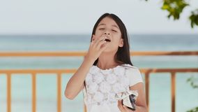 Philippine schoolgirl in white dress smiles, eating crispy potato chips. Tropical landscape. The palms. Summer. Philippine schoolgirl in white dress smiles stock video footage