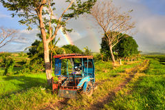 Philippine tricycle. Sun rising over a rice field in Bicol province, Philippines with a double rainbow and mountain in the background Royalty Free Stock Photography