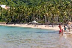 02/06/2019 - Philippinen, Insel Palawan, EL Nido: Tropischer Strand mit hohen Bäumen und Entspannungsleuten Meerblick mit Tourist lizenzfreies stockbild