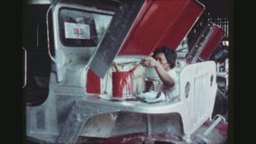 Employee Paints A Jeepney. PHILIPPINES, CITY OF LAS PINAS, APRIL 1978. A Male Employee Paints The Inside Of A Bonnet Of An Assembled Jeepney In A Bright Red stock footage