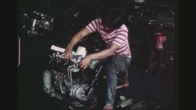 Worker Assembles A Motor Engine. PHILIPPINES, CITY OF LAS PINAS, APRIL 1978. A Male Worker Looks At The Camera And Assembles A Part On A Motor Engine Of A stock video footage
