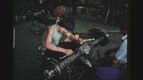 Employees Assembling Axle. PHILIPPINES, CITY OF LAS PINAS, APRIL 1978. Two Shot Sequence Of Male Employees Assembling Parts Of A Wheel Axle Of Jeepneys Inside stock video