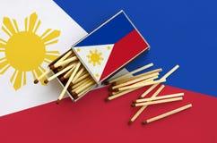 Philippines diminuent est montrées sur une boîte d'allumettes ouverte, de laquelle plusieurs matchs tombent et des mensonges sur  photos libres de droits