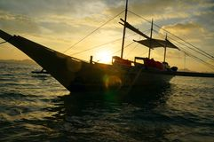 Philippines fisher boat in sunset. A typical, local transportation boat in the philippines, ankered at the beach with sunset in the back Royalty Free Stock Photos