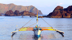 Philippines fishing boat. A traditional fishing boat (banca), powered by a small gasoline engine floating on water at the seashore of claveria, philippines Royalty Free Stock Photos