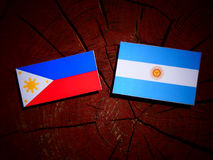 Philippines flag with Argentinian flag on a tree stump  Royalty Free Stock Images