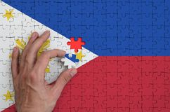 Philippines flag is depicted on a puzzle, which the man`s hand completes to fold.  vector illustration