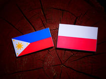 Philippines flag with Polish flag on a tree stump isolated. Philippines flag with Polish flag on a tree stump vector illustration