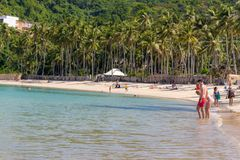 02/06/2019 - Philippines, island Palawan, El Nido: Tropical beach with tall trees and relaxing people. Seascape with tourists. 02/06/2019 - Philippines, island royalty free stock image