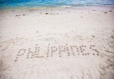 Philippines written in a sandy tropical beach Stock Photos