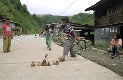 Philippinische Jungen spielen mit ihren Oberteilen auf der Straße Lizenzfreies Stockbild