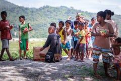 Philippinische Kinder, die in einer Linie stehen und Snack in ihrem halten Stockfotografie