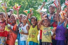 Philippinische Kinder, die in einer Linie stehen und Snack in ihrem halten Lizenzfreie Stockbilder