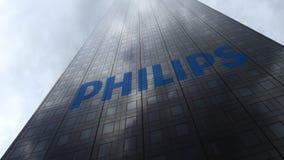 Philips-embleem op een wolkenkrabbervoorgevel die op wolken wijzen Het redactie 3D teruggeven Stock Fotografie