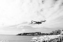 Philipsburg, Sint Maarten - 24 de janeiro de 2016: mosca do voo do jato baixa sobre a praia do maho Terra plana no céu nebuloso A Fotos de Stock Royalty Free
