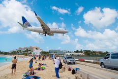 Philipsburg, Sint Maarten - February 13, 2016: airplane land over people on maho beach. Plane low fly on cloudy blue sky. Jet flig. Ht over sea. Beach vacation royalty free stock photos