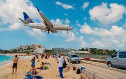 Philipsburg, Sint Maarten - February 13, 2016: airplane land over people on maho beach. Plane low fly on cloudy blue sky. Jet flight over sea. Beach vacation stock images