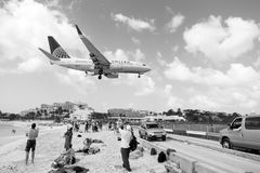 Philipsburg, Sint Maarten - February 13, 2016: airplane land over people on maho beach. Plane low fly on cloudy blue sky. Jet flight over sea. Beach vacation royalty free stock photos