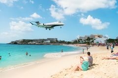 Philipsburg, Sint Maarten - February 13, 2016: jet flight land over maho beach. Plane low fly on cloudy blue sky. Airplane over people on sea. Beach vacation stock images