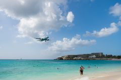Philipsburg, Sint Maarten - February 13, 2016: plane land over maho beach. Jet flight low fly in cloudy sky. Airplane on blue sea. Beach vacation at Caribbean royalty free stock photo