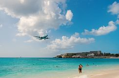 Philipsburg, Sint Maarten - February 13, 2016: plane land over maho beach. Jet flight low fly in cloudy sky. Airplane on. Blue sea. Beach vacation at Caribbean royalty free stock image