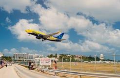 Philipsburg, Sint Maarten - February 13, 2016: plane low fly over maho beach. Jet flight land on cloudy blue sky. Philipsburg, Sint Maarten - February 13, 2016 royalty free stock photos