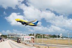 Philipsburg, Sint Maarten - February 13, 2016: plane low fly over maho beach. Jet flight land on cloudy blue sky. Airplane in sunn. Philipsburg, Sint Maarten stock image