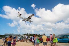 Philipsburg, Sint Maarten - February 13, 2016: wanderlust, travel and trip. Plane land over maho beach. Jet flight low fly on clou. Dy blue sky. Airplane in royalty free stock photo