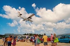Philipsburg, Sint Maarten - February 13, 2016: wanderlust, travel and trip. Plane land over maho beach. Jet flight low. Fly on cloudy blue sky. Airplane in royalty free stock images
