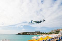 Philipsburg, Sint Maarten - January 24, 2016: jet flight low fly over maho beach. Plane land on cloudy sky. Airplane over people a. T blue sea. Wanderlust stock photography