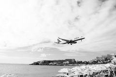 Philipsburg, Sint Maarten - January 24, 2016: jet flight low fly over maho beach. Plane land on cloudy sky. Airplane. Over people at blue sea. Wanderlust royalty free stock photos