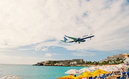 Philipsburg, Sint Maarten - January 24, 2016: jet flight low fly over maho beach. Plane land on cloudy sky. Airplane. Over people at blue sea. Wanderlust royalty free stock photography