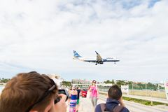 Philipsburg, Sint Maarten - January 24, 2016: vacation on maho beach at Caribbean. Plane low fly over people. Jet flight land on c. Loudy sky. Airplane in sunny stock image