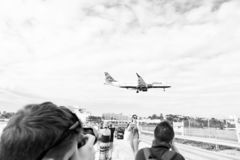 Philipsburg, Sint Maarten - January 24, 2016: vacation on maho beach at Caribbean. Plane low fly over people. Jet flight. Land on cloudy sky. Airplane in sunny stock images
