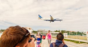 Philipsburg, Sint Maarten - January 24, 2016: vacation on maho beach at Caribbean. Plane low fly over people. Jet flight. Land on cloudy sky. Airplane in sunny royalty free stock image