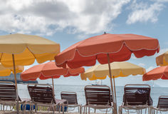Philipsburg St. Maarten beach umbrellas. Philipsburg St. Maarten orange and yellow beach umbrellas. Beach chairs facing ocean views Stock Photos