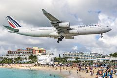 Maho Beach, Philipsburg, Sint Maarten. PHILIPSBURG, SINT MAARTEN - DECEMBER 30, 2013: A commercial jet approaches Princess Juliana airport above onlookers on Royalty Free Stock Image